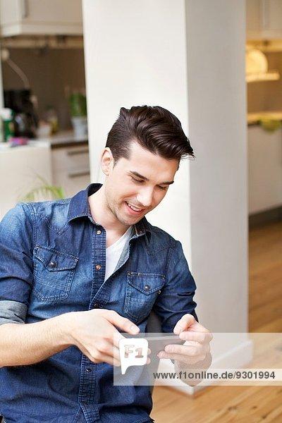 Junger Mann sucht Smartphone in der Küche