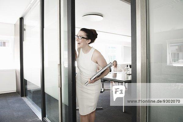 Junge Geschäftsfrau wartet am Eingang zum Konferenzraum