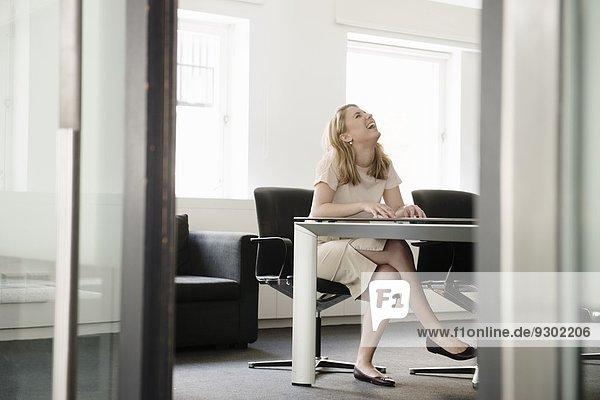 Junge Geschäftsfrau lacht im Sitzungssaal