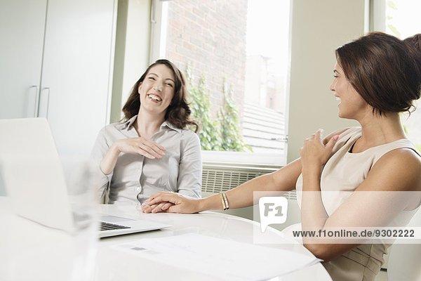 Zwei Geschäftsfrauen lachend im Büro