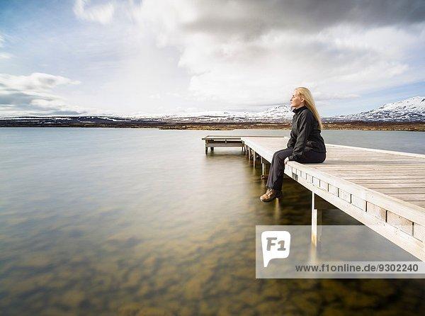 Mittlere erwachsene Frau mit Blick vom Pier  Thingvellir  Island