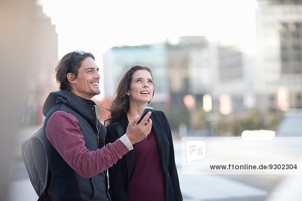 Paar mit Smartphone  das auf der Straße nach oben schaut
