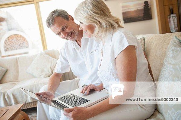 Paar mit Laptop im Hotelzimmer