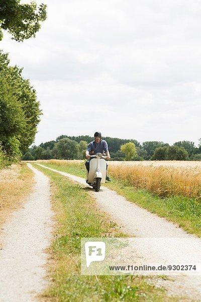 Erwachsener Mann fährt Motorroller entlang der Piste mit einer Tochter  die sich an der Taille festhält.