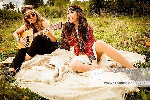 Hippy Girls auf Decke im Feld  Gitarre spielen