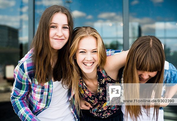 Portrait of three young women laughing in front of glass office building