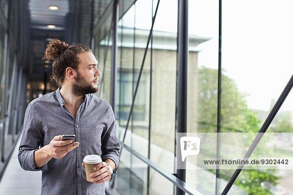 Mann mit Smartphone in der Kaffeepause