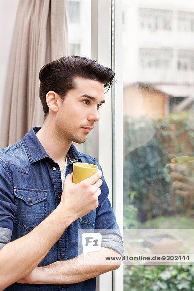 Porträt eines jungen Mannes  der durch die Terrassentür blickt.