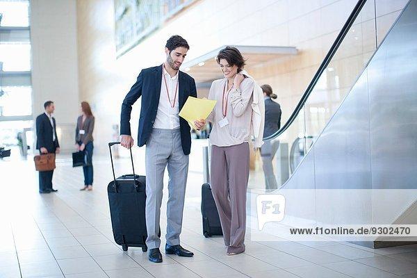 Geschäftsmann und Geschäftsfrau bei der Ankunft im Atrium des Konferenzzentrums