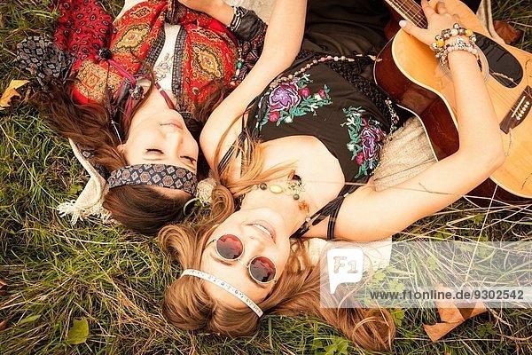 Hippy Girls im Feld liegend mit Gitarre
