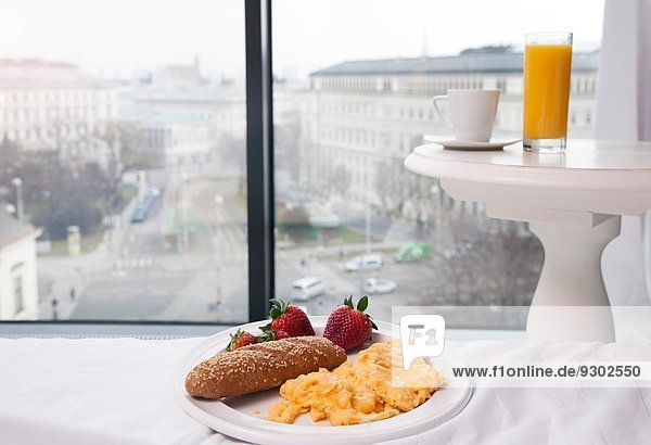 Breakfast of scrambled eggs  juice and coffee by hotel window with view  Vienna  Austria