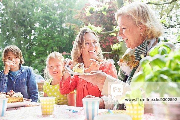 Mutter serviert Geburtstagskuchen für die Familie auf der Geburtstagsfeier