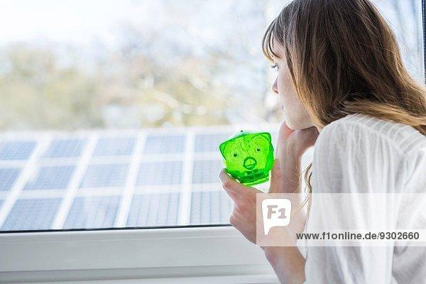 Frau mit grünem Sparschwein beim Blick durchs Fenster