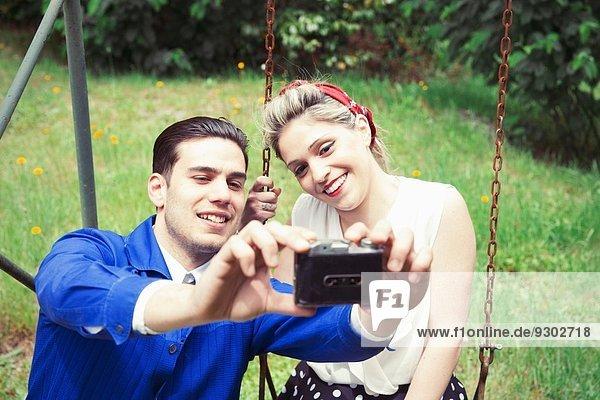 Junges Vintage-Paar mit Selfie-Kamera im Garten