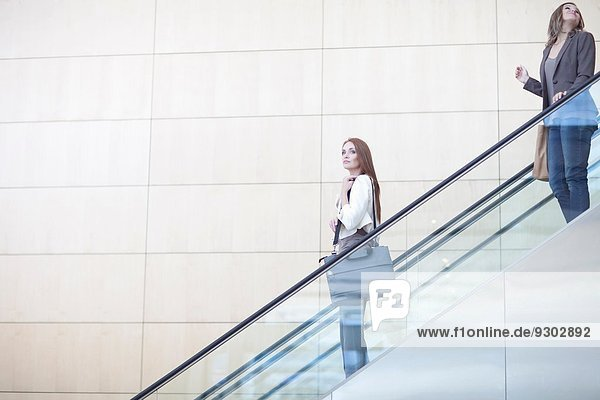 Geschäftsfrauen fahren mit dem Aufzug des Konferenzzentrums nach unten