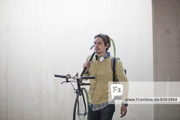 Mittlerer Erwachsener Mann mit Fahrrad durch die Stadtunterführung