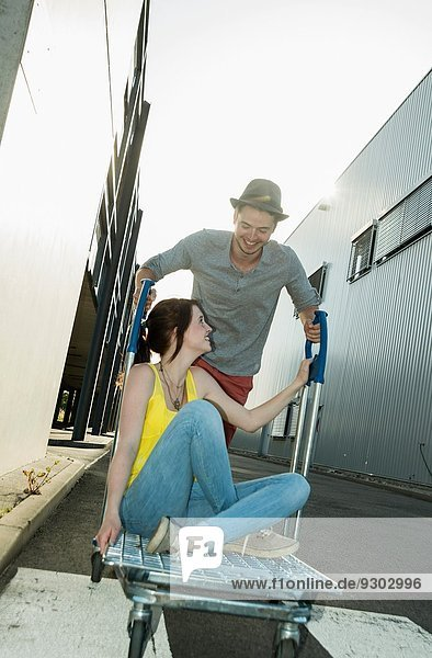 Junges Paar  das auf dem Einkaufswagen in der Straße herumalbert.