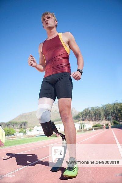Sprinter stehend mit Beinprothese auf dem