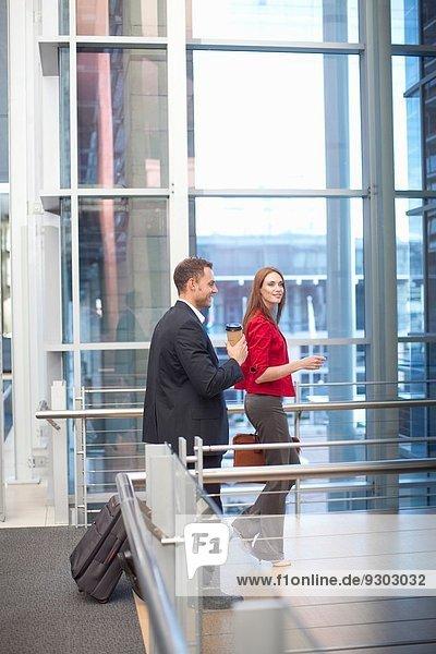 Mittlere erwachsene Geschäftsfrau und Kollegin auf dem Laufsteg des Konferenzzentrums