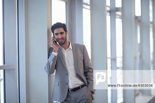 Junge Geschäftsleute chatten auf dem Smartphone im Konferenzzentrum