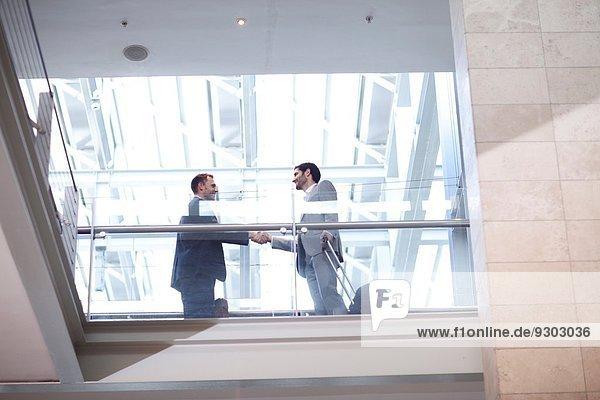 Zwei junge Geschäftsleute beim Händeschütteln auf dem Balkon des Konferenzzentrums