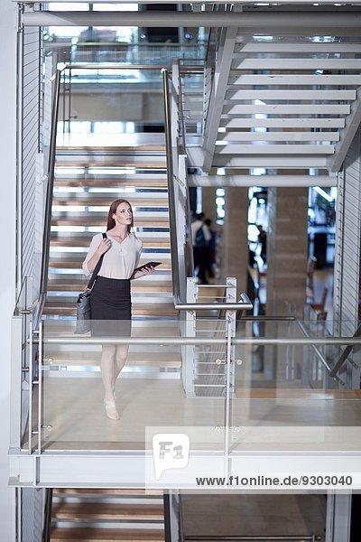 Mittlere erwachsene Geschäftsfrau auf der Treppe im Konferenzzentrum