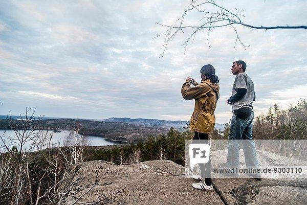 Junges Paar auf dem Gipfel einer Felsformation fotografiert die Aussicht