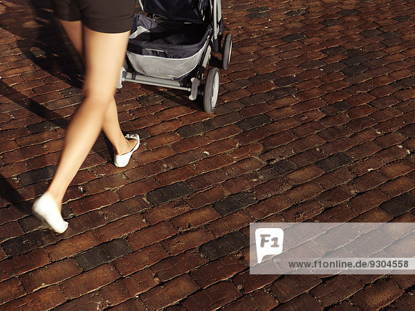 Frau schiebt einen Kinderwagen über mit Backstein gepflasterte Straße  Nahaufnahme der Beine Frau schiebt einen Kinderwagen über mit Backstein gepflasterte Straße, Nahaufnahme der Beine