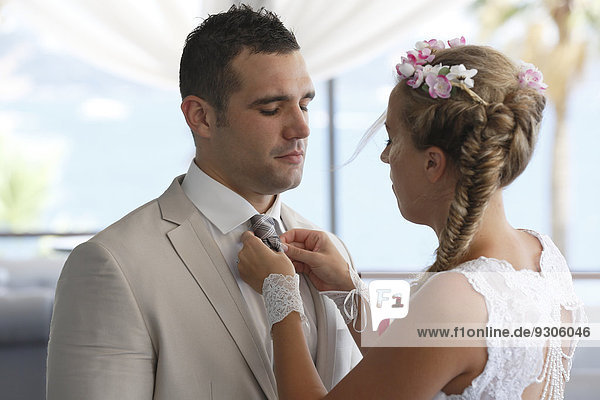 Braut rückt dem Bräutigam die Krawatte zurecht