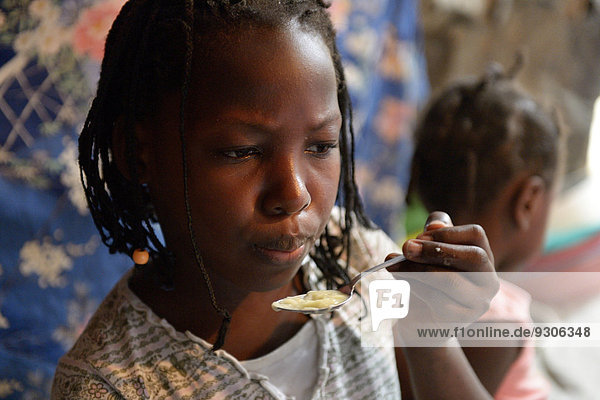 Girl  9 years  eating soup in a shack  Camp Icare for earthquake refugees  Fort National  Port-au-Prince  Haiti