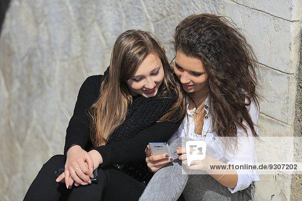 Zwei Freundinnen  Teenager  sitzen angelehnt an eine Mauer und lesen eine SMS auf dem Handy  Menton  Provence-Alpes-Côte d?Azur  Frankreich