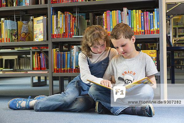 Zwei Kinder beim Lesen in einer öffentlichen Bibliothek  Stadtbibliothek  Coswig  Sachsen  Deutschland