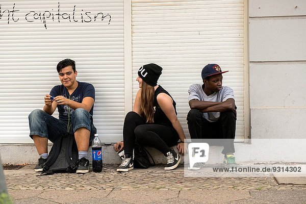 West-Berlin  Berlin  Germany. Three youngsters  sitting at the doorstep of a store  which is closed with shutters and blinds.