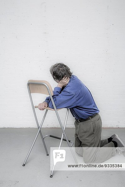 Man leaning on a chair.
