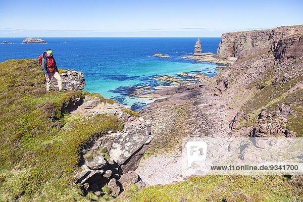 Frau wandert durch Küstenlandschaft im Nordwesten Schottlands nahe der Sandwood Bay