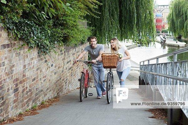 Radfahrerpaar schiebt Fahrrad am Kanal entlang  London  UK