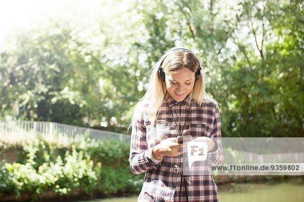 Frau hört Musik am Kanal
