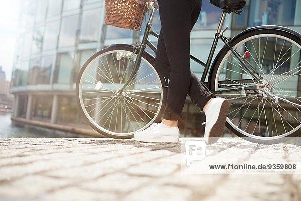 Frau schiebt Fahrrad am Kanal entlang