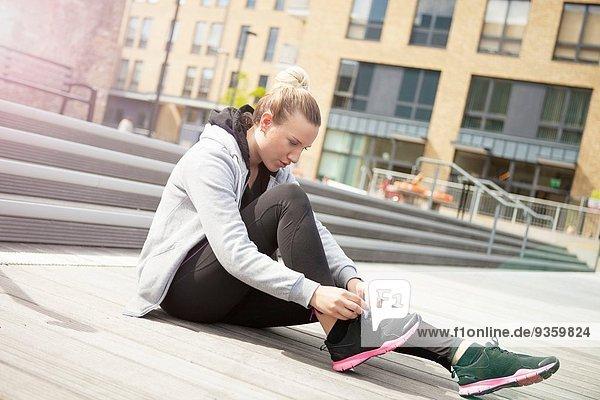 Frau auf dem Boden sitzend Schnürsenkel bindend