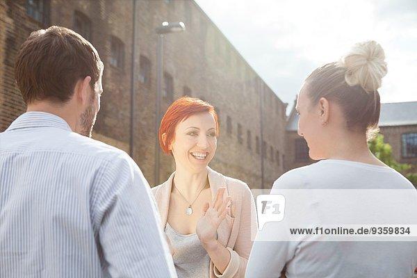 Drei junge Leute  die draußen reden.