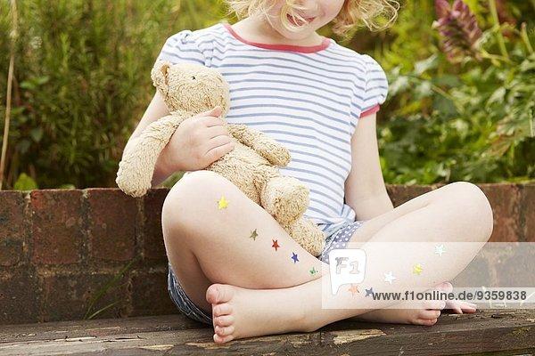 Mädchen auf Gartensitz mit Sternaufklebern an den Beinen