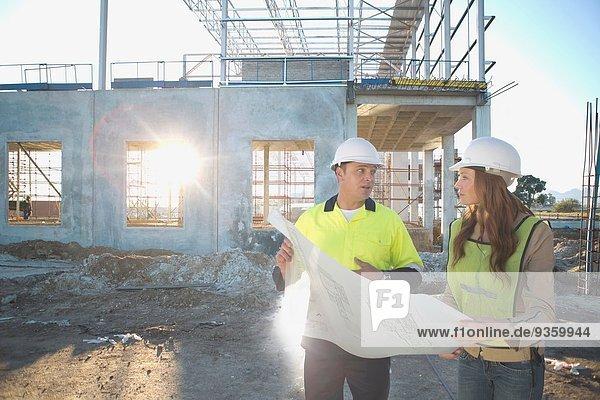 Bauleiter und Architekt im Gespräch über den Bauplan auf der Baustelle