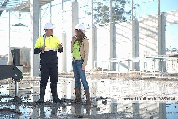 Bauleiter und Architekt im Gespräch auf der Baustelle