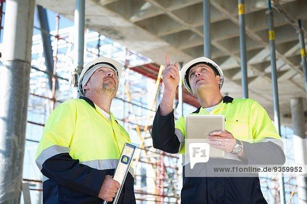 Bauleiter und Bauherr sucht auf der Baustelle