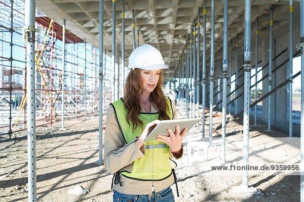 Bauleiter mit Touchscreen auf digitalem Tablett auf der Baustelle