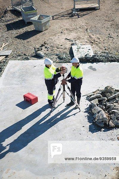 Hochwinkelansicht des Bauleiters und Vermessers auf der Baustelle