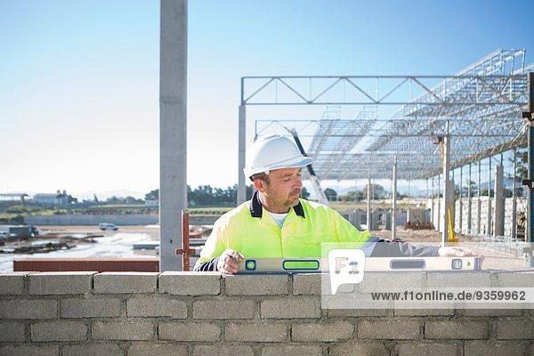 Bauherr mit Wasserwaage an der Baustellenwand