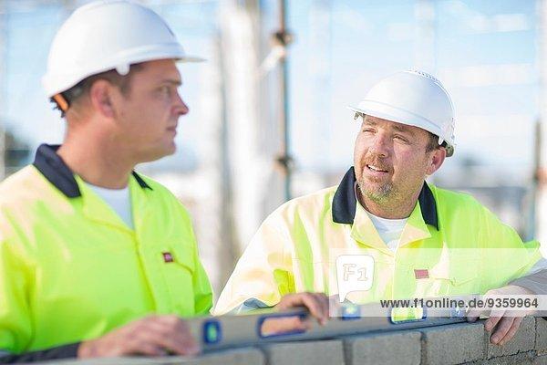Bauherr und Bauleiter mit Wasserwaage an der Baustellenwand