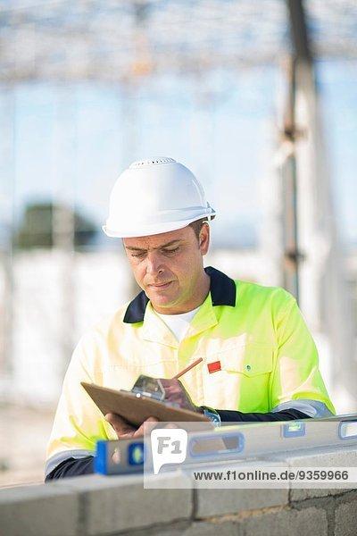 Bauleiter prüft Wasserwaage an der Baustellenwand