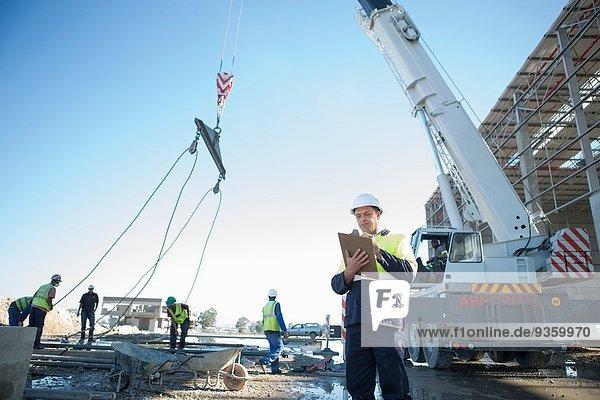 Bauleiter mit Zwischenablage auf der Baustelle